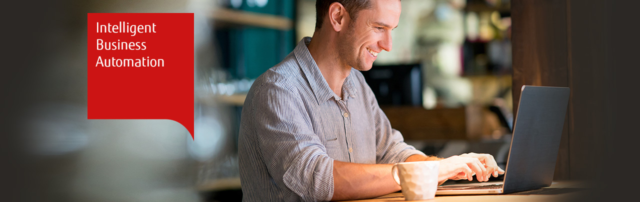 Photo of a smiling man using a laptop