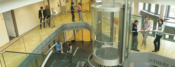 An atrium with wood floored wlakways and a glass lift, small groups people are talking