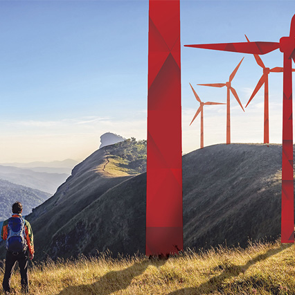Man looking out at a hill with origami wind turbines