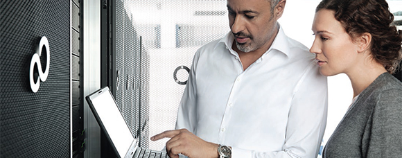 Man and a woman looking at a Fujitsu Laptop while standing next to a Fujitsu server in a server room