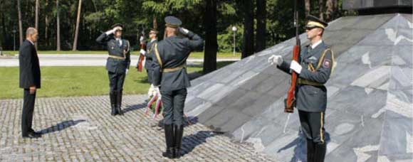 slovenian military paying their respects at a memorial.