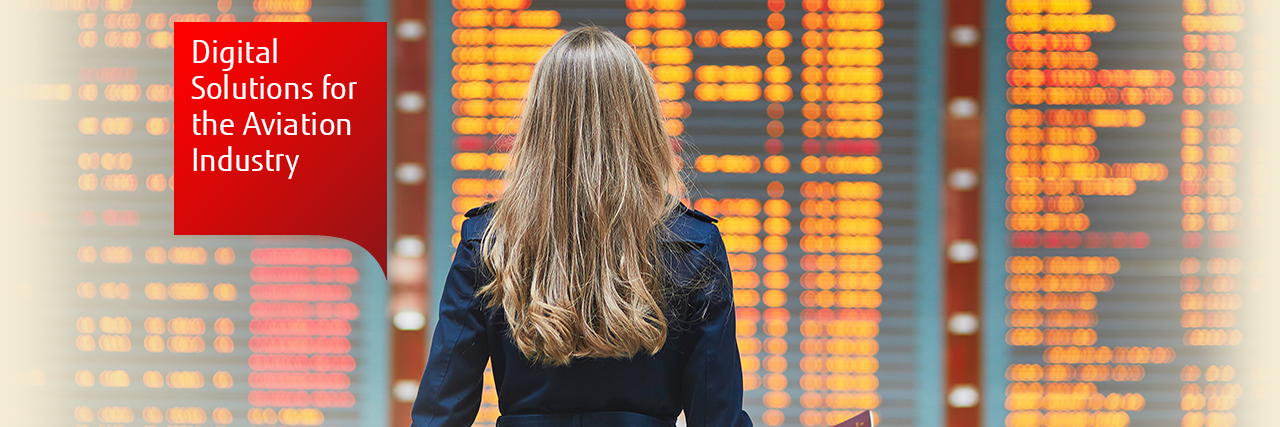 Photo of a woman looking at a flight information screen at an airport