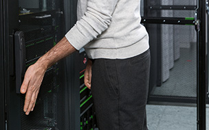 Photo of a person using a PalmSecure scanner to access a server.