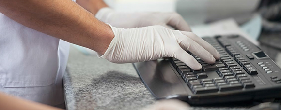 A doctor with ruber gloves typing on a keyboard
