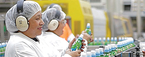 two women at a bottling plant. one holding a bottle just off the production line