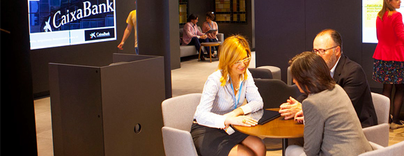 A female CaixaBank worker with a Fujitsu tablet sitting at a table talking to a man and a women