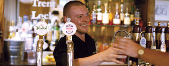 Barman passing a pint to a customer