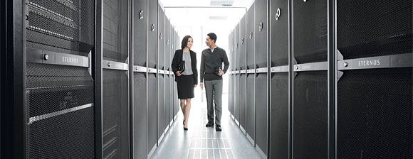2 business people walking between server racks