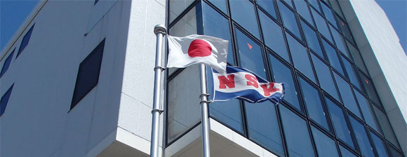 Flags of Japan and NSK in front a glass office building