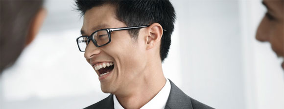 A man with glasses laughing