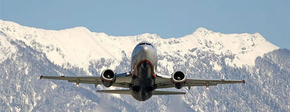 An airliner in flight with snow capped mountains behind