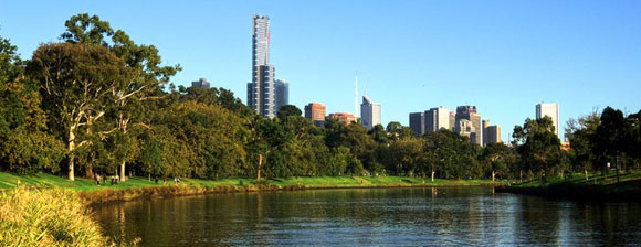 Melbourne skyline behind a lake and trees