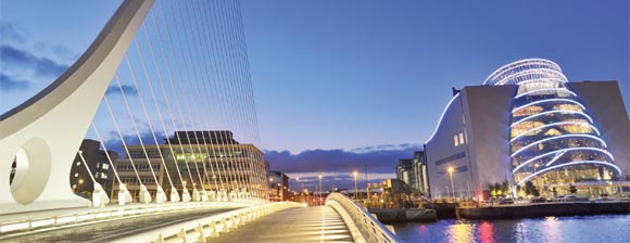 A night view of the glass fronted Dublin convention centre over the interestingly curved Samual Becket Suspension bridge