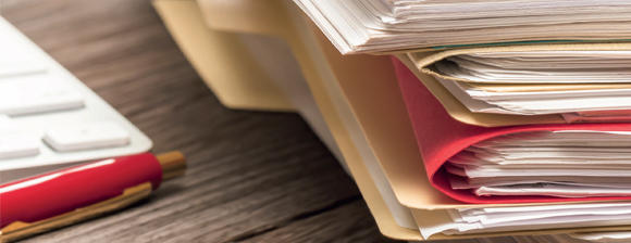 Close up shot of a stack of paper files on a desk next to a red pen