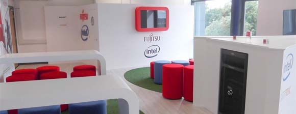 A white room with colourful seating & interesting shaped funiture surrounding a Fujitsu Intel Server