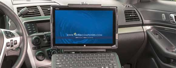 A notbook computer mounted to a police car dash