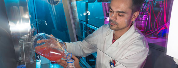 A man wearing a white coat pouring red liquid in a lab