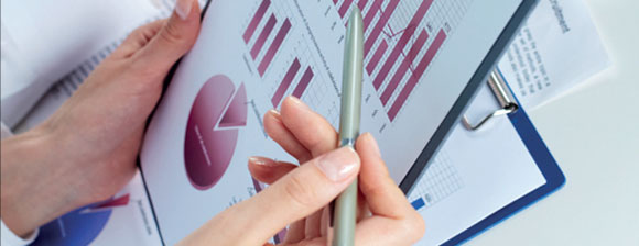 A woman holding a pen, checking a page of charts on a clipboard