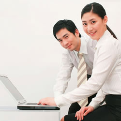 photograph of man and woman with laptop