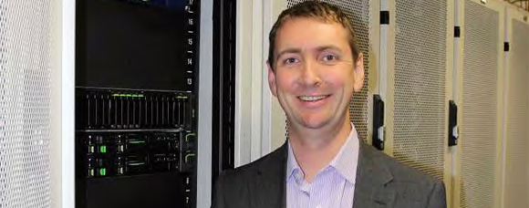 Man in a server room smiling into the camera
