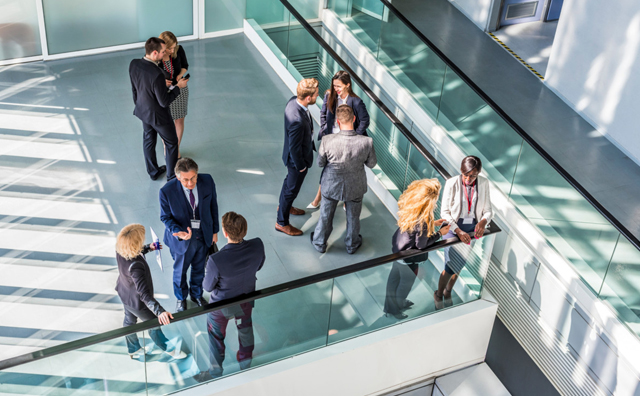 People stood in an office talking to each other - photo taken from above.