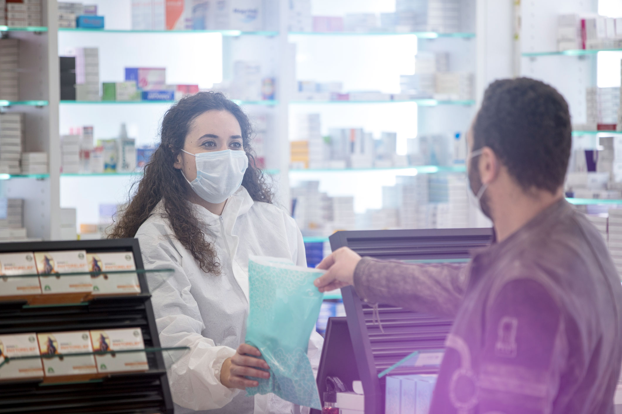Customer collects a prescription from pharmacist wearing ppe