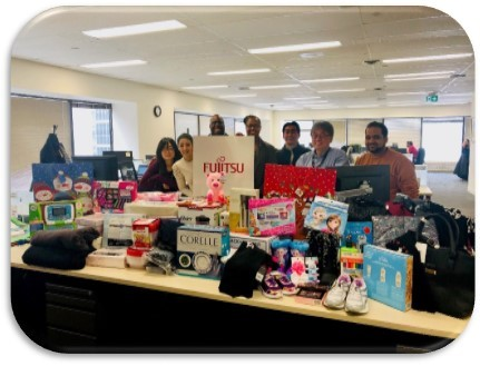 Photo of donated gifts with some of the Fujitsu US employees
