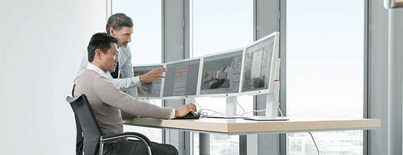 2 men in a bright office, 1 sitting and 1 standing, looking at 4 computer displays