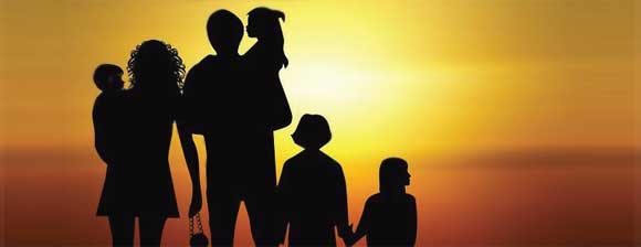 A family in silhouette standing in front of a sunset