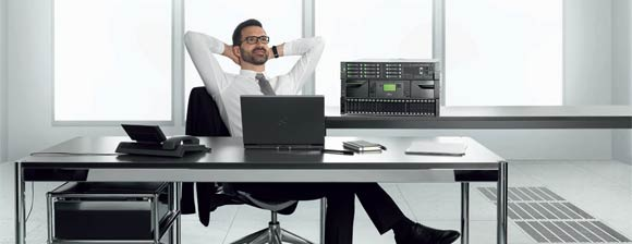 A man looking relaxed in a modern looking office in front of a stack of Fujitsu ETERNUS & PRIMERGY equipment