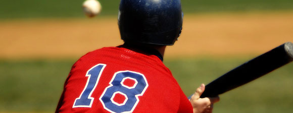 Baseball player wearing a red baseball shirt with the number 18 on the back swinging for the ball