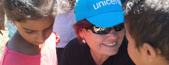 A smiling UNICEF worker with 2 children