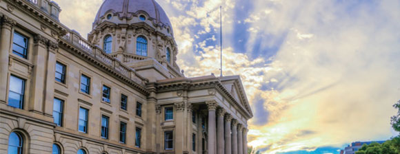 A cloudy but blue sky with sun shining through behind the Alberta Legislature building in Edmonton