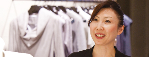 A smiling woman in front of a rack of clothes