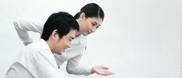 A man and a woman gesturing at a notebook PC
