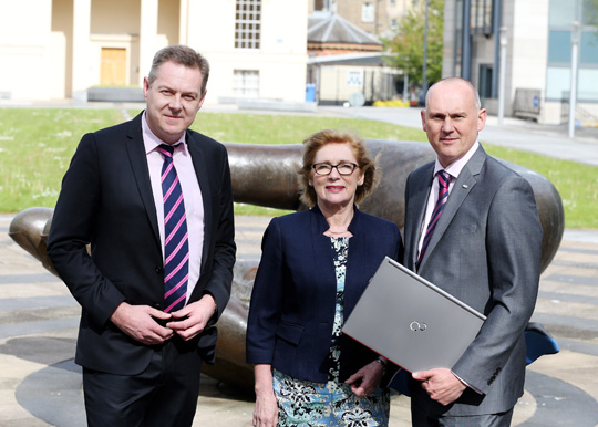 Paul Roche, Managing Director,  SmartSchools,  Minister for the Department of Education and Skills, Jan O'Sullivan and Paul Frost, Channel Manager, Fujitsu Enterprise Products on a sunny day standing in front of a sculpture