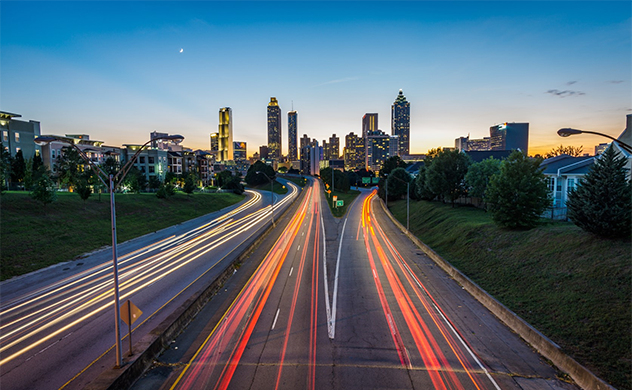 Motion-blur photo of traffic on roads in front of Atlanta, USA, skyline.