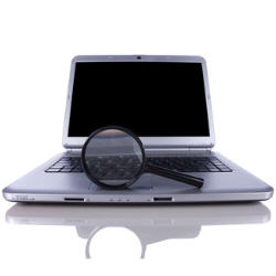 Photograph of a magnifying glass and a laptop