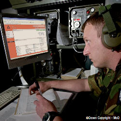 Photograph of man in uniform using a computer