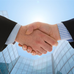 Photograph of a handshake in front of a modern office building