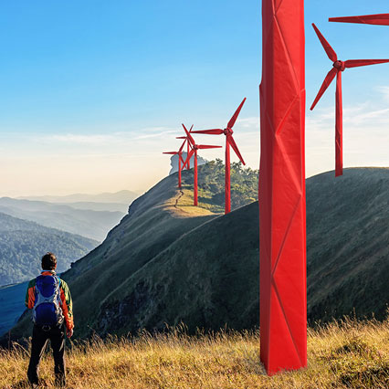 man looking at origami wind turbines