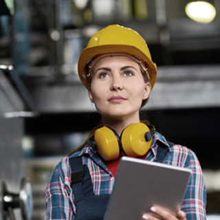 Woman wearing safety had and headphones - Health and Safety