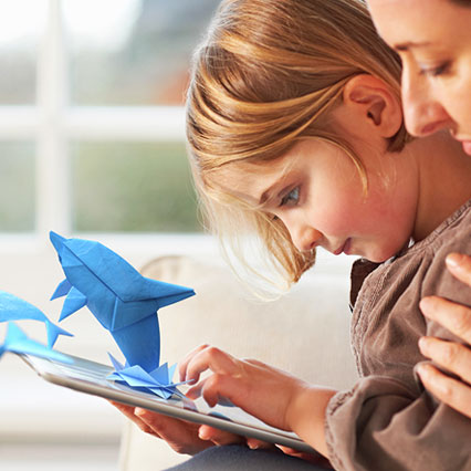 child using tablet with origami dolphins