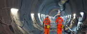 2 Crossrail workers in orange overalls walking down a tunnel