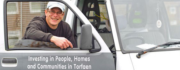 man leaning on the door of a white van smiling into the camera. caption on the side of the van reads: investing in people, homes and communities in torfaen