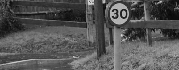 Black and white photo of a 30mph road sign with flood water flowing past it
