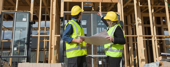Two workers looking at building plans with a building being constructed in the background