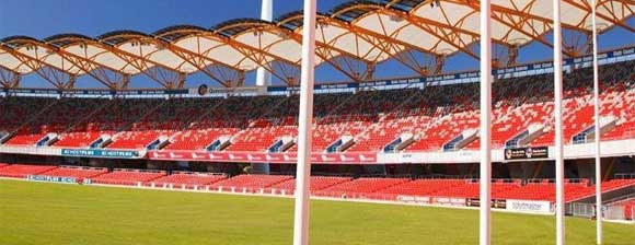 Inside of the Metricon Stadium showing posts, the pitch and red stadium seats
