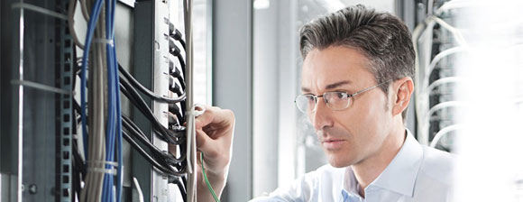 A man with glasses working with network cabling