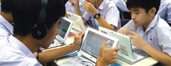 Pupils sitting at desks using tablet computers, some are wearing headphones